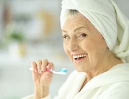 An older woman brushing her teeth