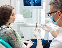 Dentist showing patient an implant model