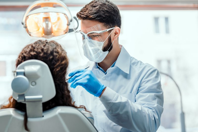 Dentist wearing PPE during dental exam