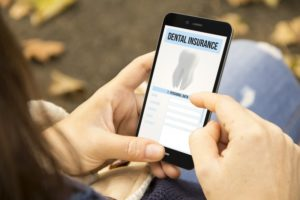 Person using phone to learn about dental insurance benefits